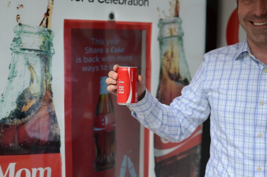 A man holds up a can of Coke after using the smile-activated Share a Coke dispenser
