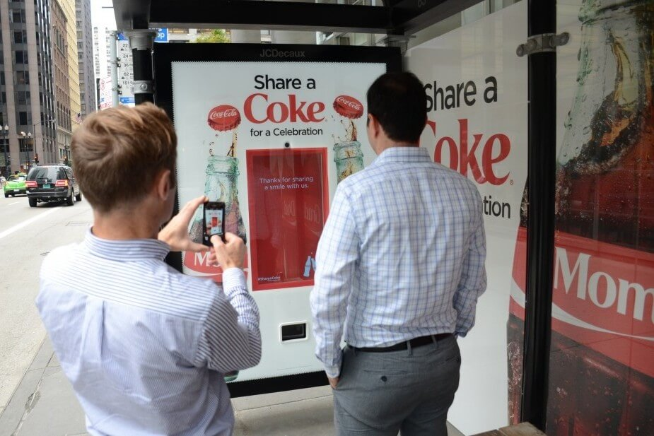 Members of the public interact with the smile-activated Coke dispenser